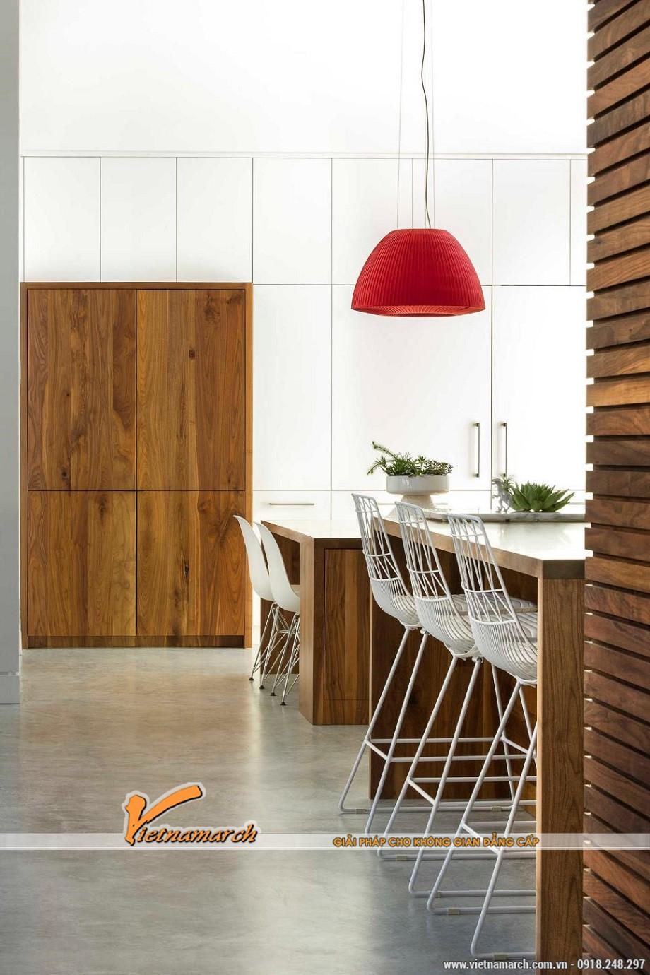 Nhà bếp này hiện đại và mới lạ ở việc kết hợp màu sắc trắng, nâu gỗ và đỏ ...