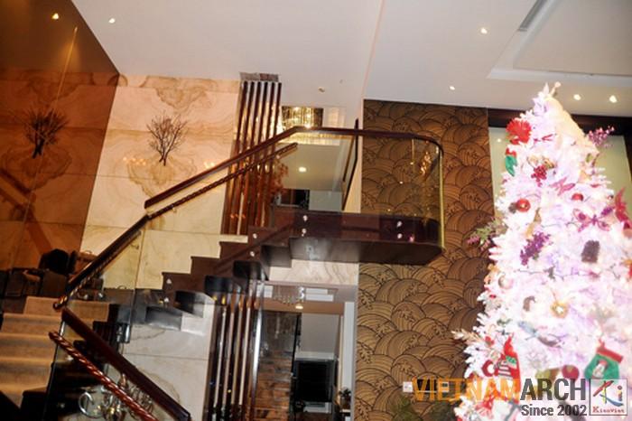 Cầu thang dẫn lên tầng 2 được làm từ gỗ và kinh, toàn bộ tường được ốp bằng đá granite cao cấp