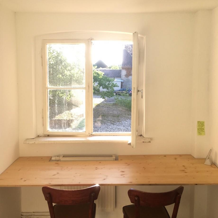 Phòng gọi điện cá nhân với bàn ghế gỗ và cửa sổ nhìn ra sân vườn