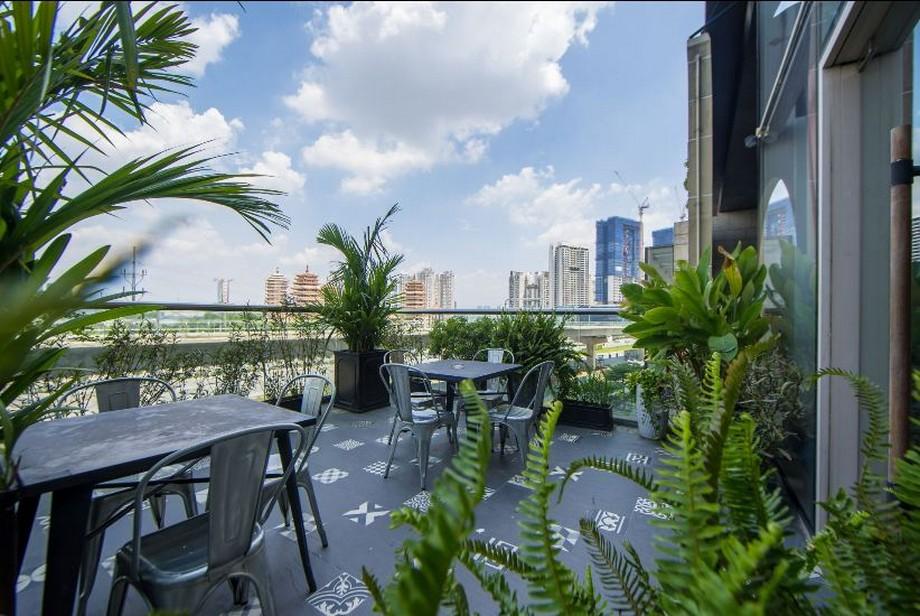 Khu vực bàn làm việc ngoài trời lý tưởng với sàn lát gạch bông cổ điển và hệ thống cây xanh tươi mát
