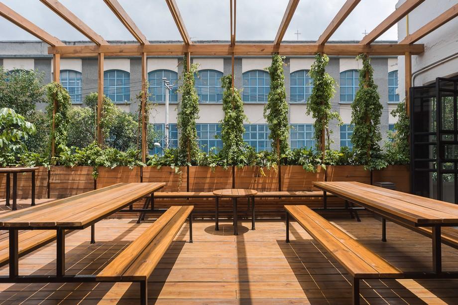Không gian đột phá ngoài trời được trang bị ghế dài và bàn bằng gỗ, và được bao phủ bởi một dàn hoa leo cây cảnh mềm mại