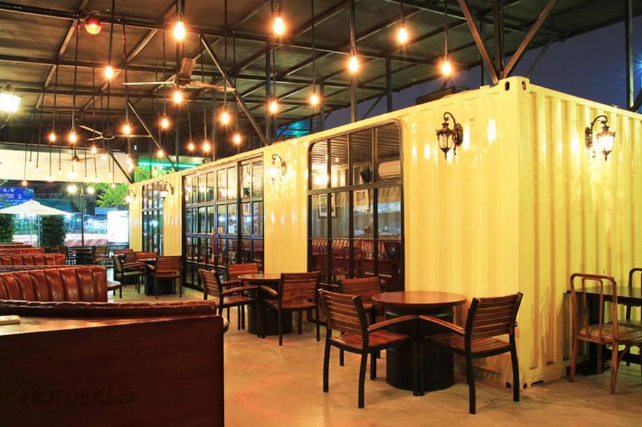 Thiết kế nhà hàng container sơn màu vàng kết hợp với các ô cửa kính và đèn treo tường thú vị