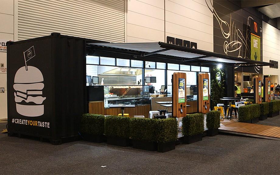Thiết kế nhà hàng container nhỏ nhắn với tông màu đen, hình ảnh đồ ăn trang trí trên thùng container và khu vực ăn uống phía ngoài thú vị