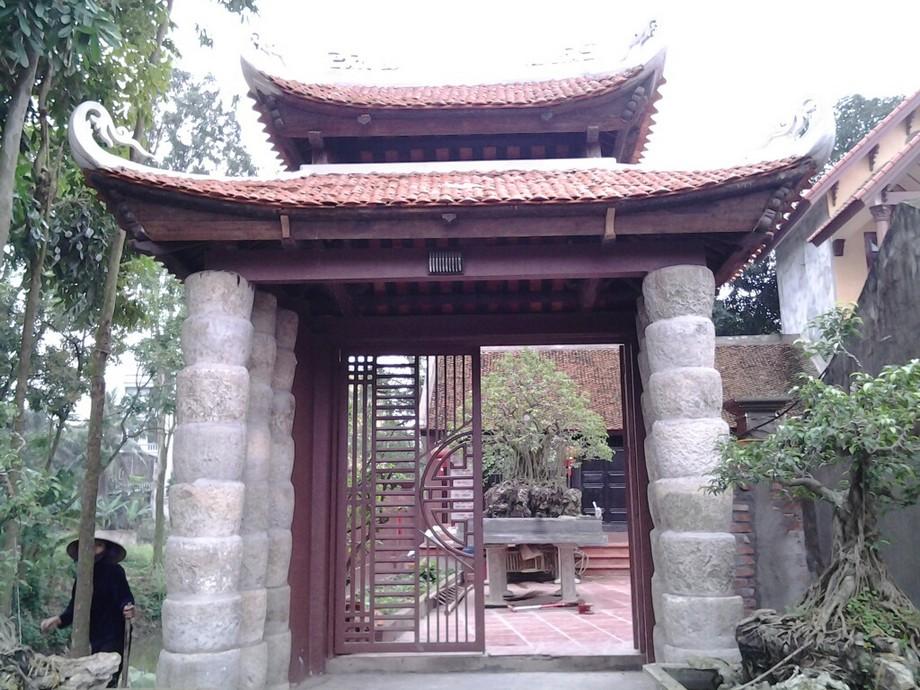 Cổng nhà gỗ đẹp với thiết kế độc đáo gồm phần mái thiết kế kiểu 4 mái và 2 hàng cột trụ bằng đá ấn tượng
