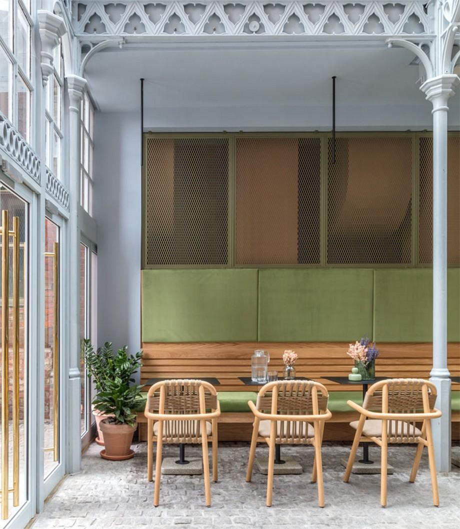 Thiết kế nội thất coworking space tại Anh với bộ bàn ghế gỗ, phía trên là các vách ngăn lưới kim loại