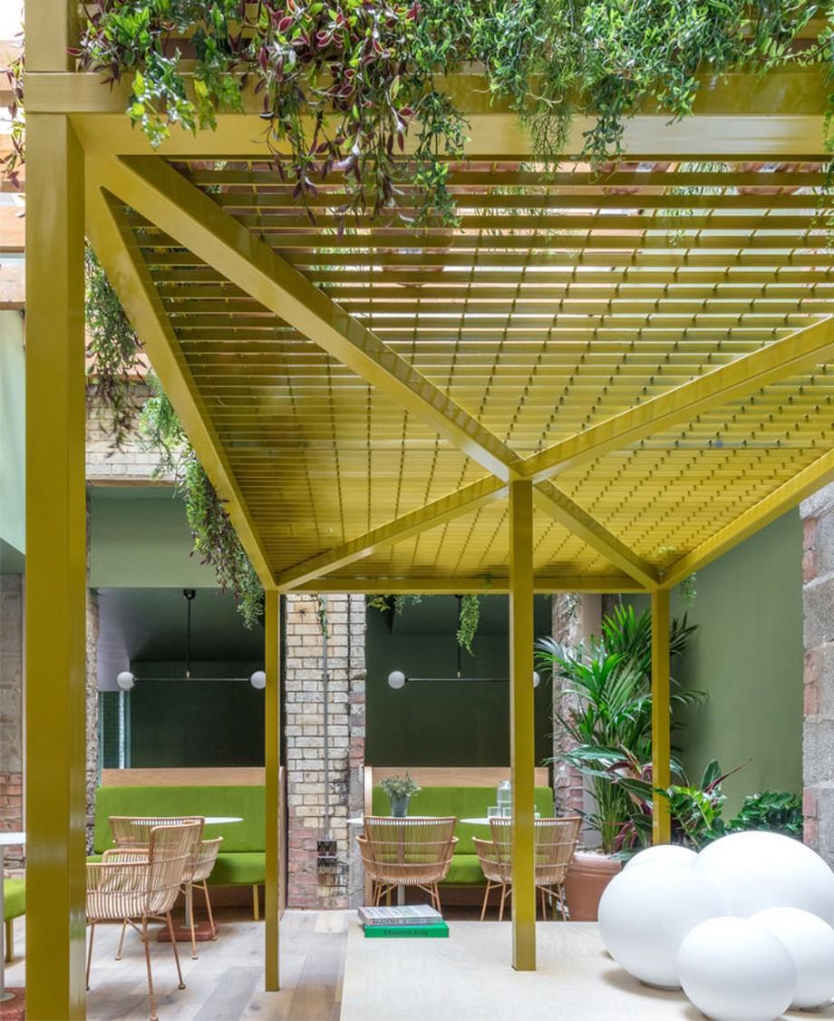Thiết kế nội thất coworking space tại Anh với bộ khung bằng kim loại được sơn vàng, trên phủ cây xanh