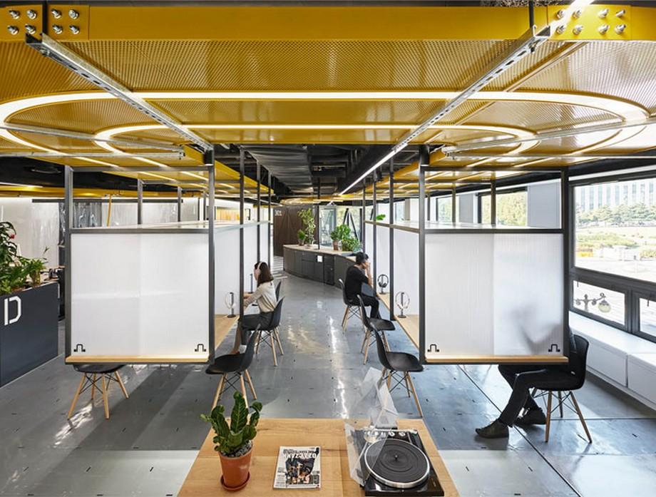 Ý tưởng trang trí nội thất văn phòng với các ô bàn làm việc cá nhân có vách ngăn và trang bị tai nghe