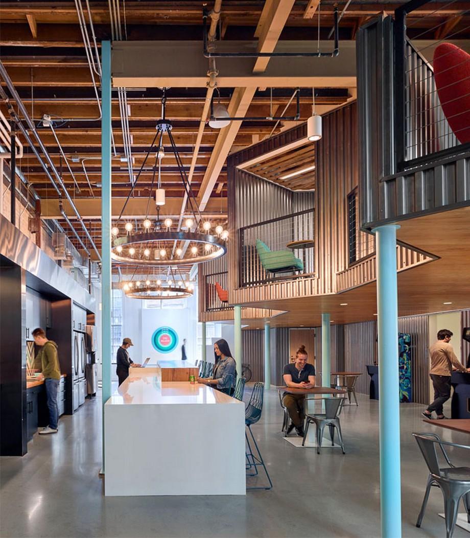 Khu vực phòng bếp của văn phòng được thiết kế với dãy bàn trắng rộng và dài, phía trên là hệ thống đèn trần, trần gỗ