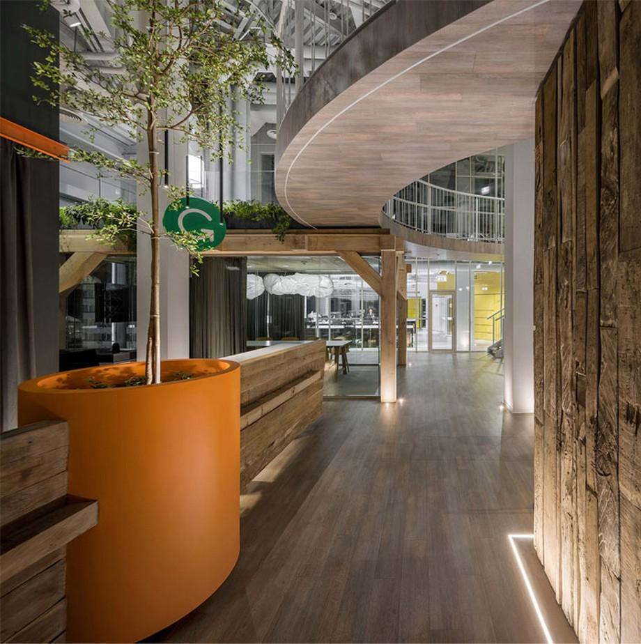 Ý tưởng trang trí nội thất văn phòng với bàn lễ tân bằng gỗ, cạnh đó là chiếc chậu cây màu cam khổng lồ