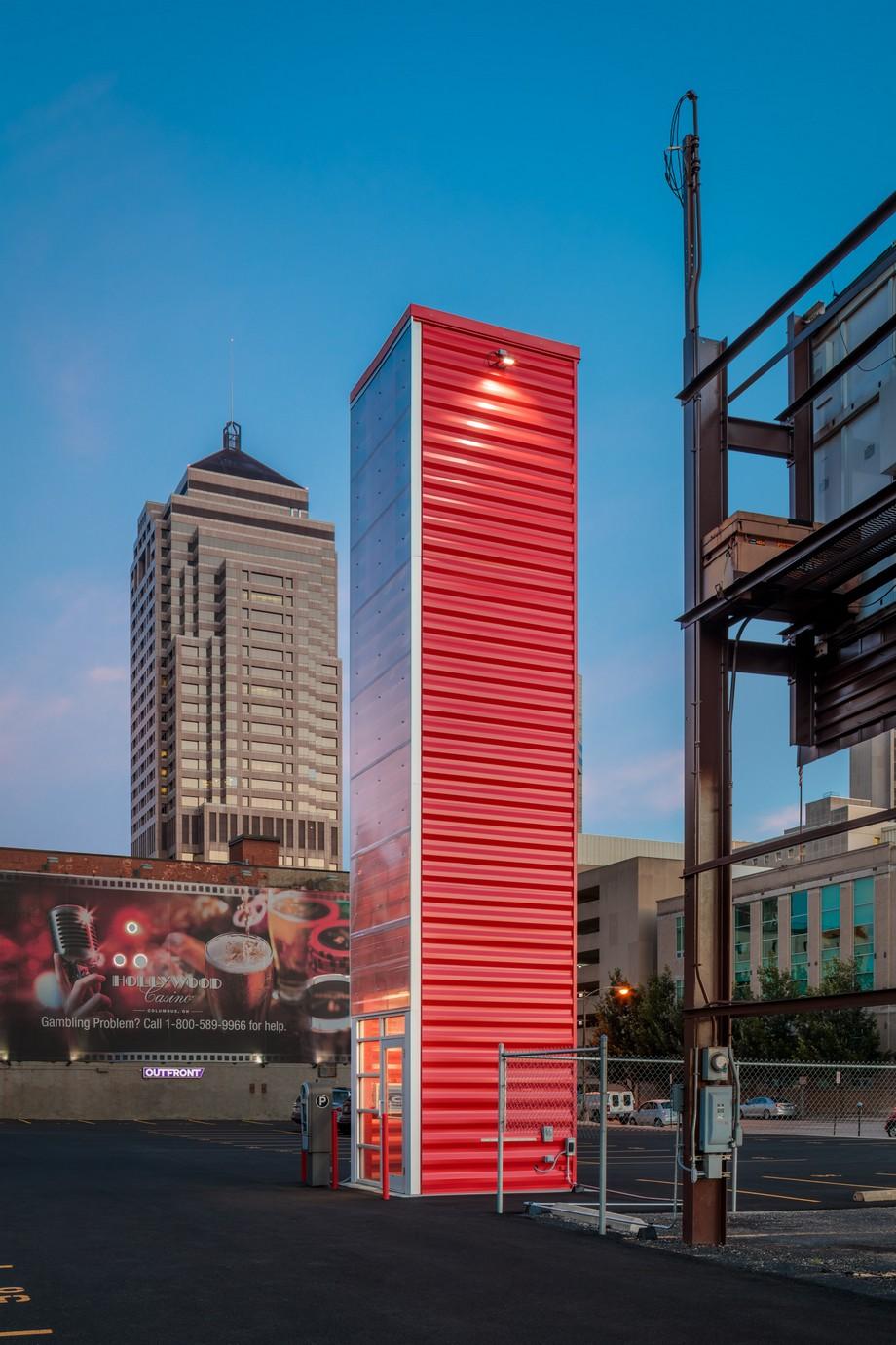 Một mặt của tòa tháp được làm từ kính trong suốt, 3 mặt còn lại là container sơn đỏ