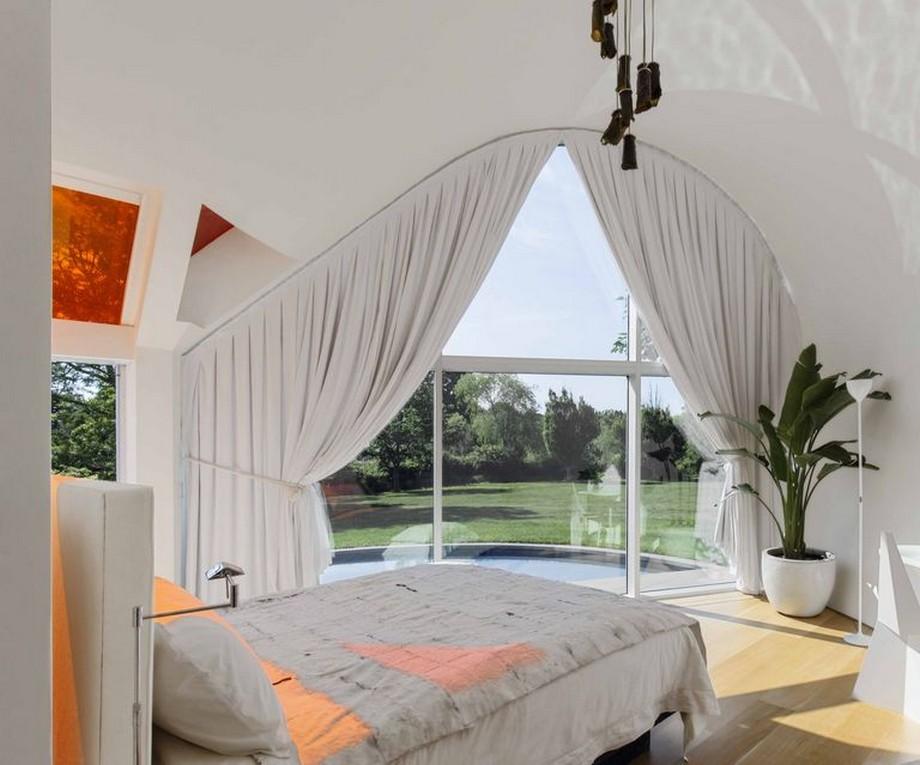 Phòng ngủ master thiết kế đơn giản với cửa kính lớn nhìn ra không gian sân vườn