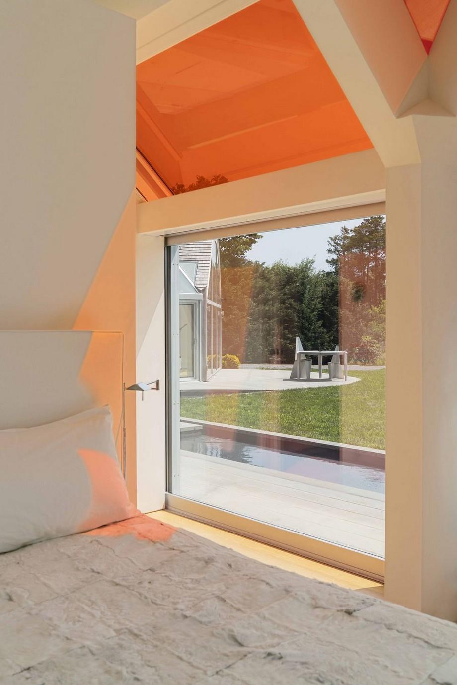 Cạnh giường ngủ là chiếc cửa sổ nhỏ và phía trên là cửa kính màu đỏ hắt ánh sáng đỏ cho không gian