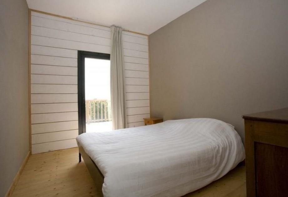 Phòng ngủ với mảng tường được ốp gỗ sơn trắng họa tiết kẻ