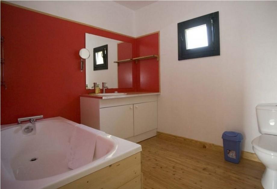 Thiết kế phòng tắm rộng rãi với sàn gỗ, bồn tằm nằm ốp gỗ bên ngoài, có 1 mảng tường sơn đổ nổi bật và chiếc tủ lavabo màu trắng