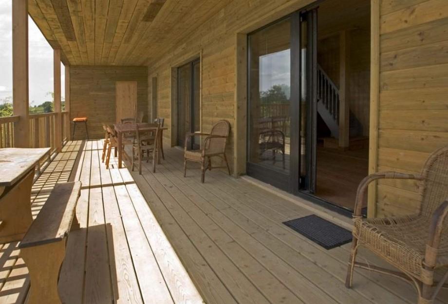 Trước khi vào không gian tầng trệt của ngôi nhà, các bạn sẽ đi qua khu vực hành lang với các bộ bàn ghế nghỉ bằng gỗ hoặc mây tre