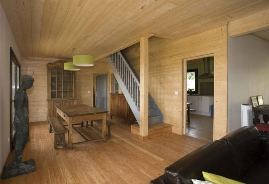 Cạnh phòng khách là không gian bàn ghế nghỉ bằng gỗ, phía trên là 2 chiếc đèn thả hình tròn màu xanh