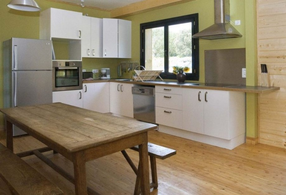 Tiến vào phòng bếp lớn, các bạn sẽ thấy một phong cách hiện đại với tủ bếp chữ L sơn trắng, mảng tường màu xanh đằng sau nổi bật