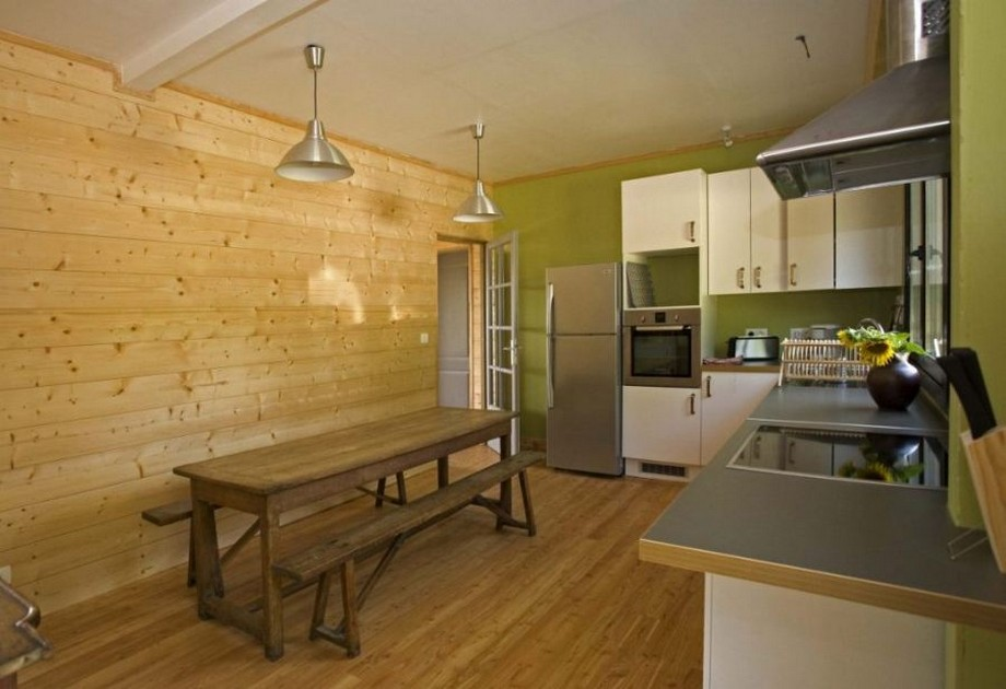 Trong phòng bếp có đặt 1 bộ bàn ghế ăn dáng dài bằng gỗ mộc, phía trên là 2 chiếc đèn thả bằng đồng