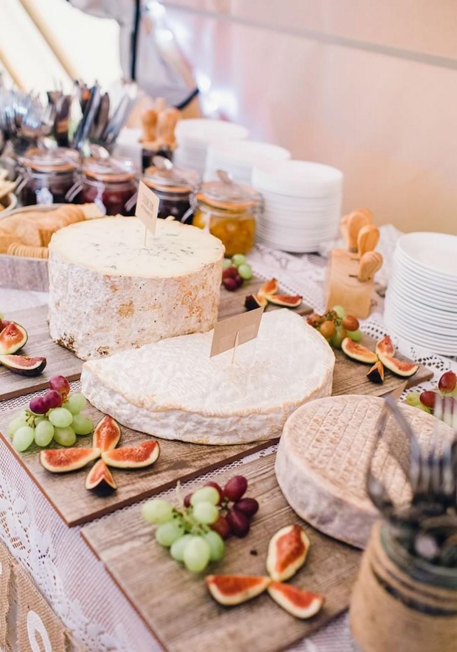 Ý tưởng trang trí hội trường tiệc cưới với bàn được trải khăn trải bàn trắng, đĩa đựng thức ăn bằng gỗ độc đáo