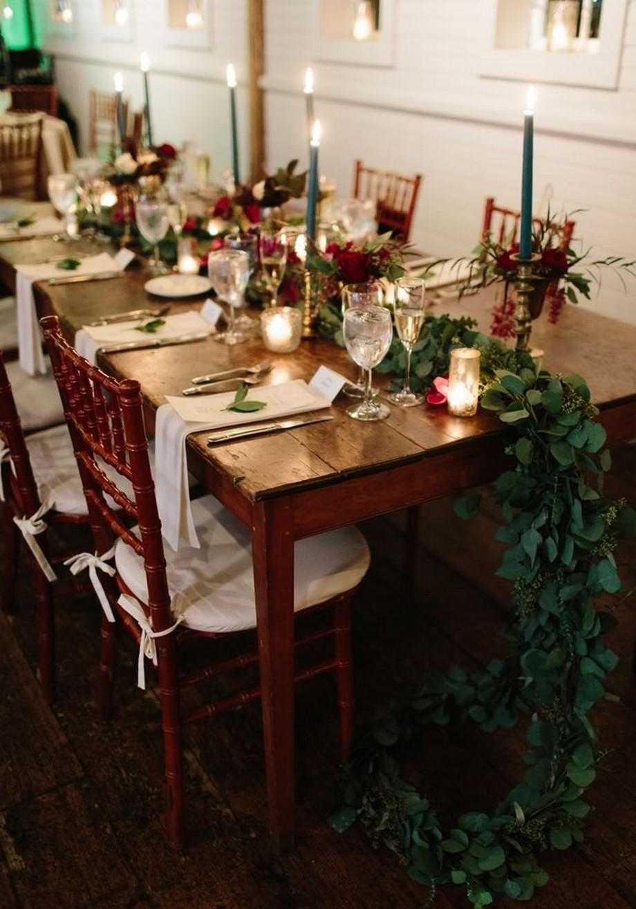 Ý tưởng trang trí hội trường tiệc cưới với khăn trải bàn từ hoa và lá chạy dài ở trung tâm bàn
