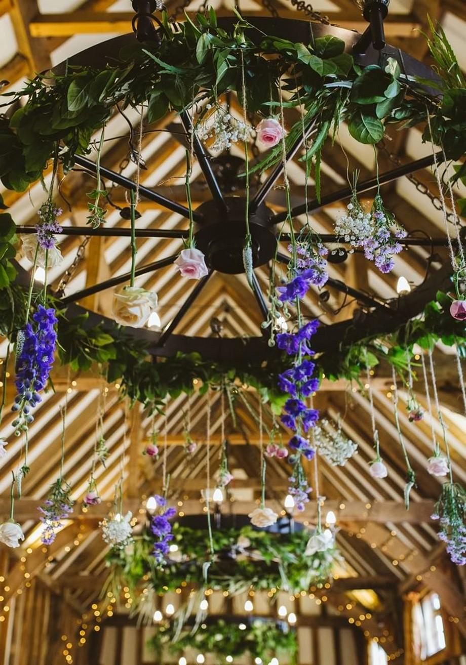 Ý tưởng trang trí hội trường tiệc cưới với những chiếc bánh xe có lá xanh và những bông hoa treo lơ lửng