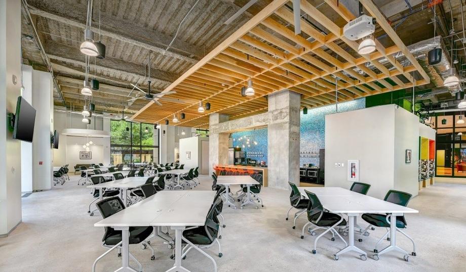 Không gian coworking hiện đại nhiều dãy bàn ghế cách xa nhau tạo không gian riêng tư